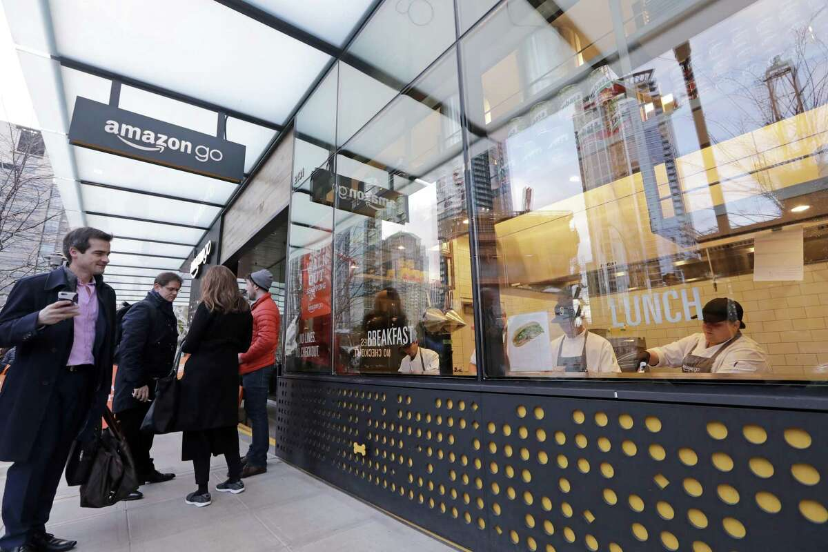 FILE- In this Jan. 22, 2018, file photo a man on the sidewalk outside watches workers prepare sandwiches inside an Amazon Go store in Seattle. Amazon?'s announcement Tuesday, Oct. 2, 2018, that it will raise its minimum wage to $15 an hour will intensify the pressure on other companies to also lift their pay levels, particularly retailers and warehouse operators that are looking to staff up for the holidays. (AP Photo/Elaine Thompson, File)