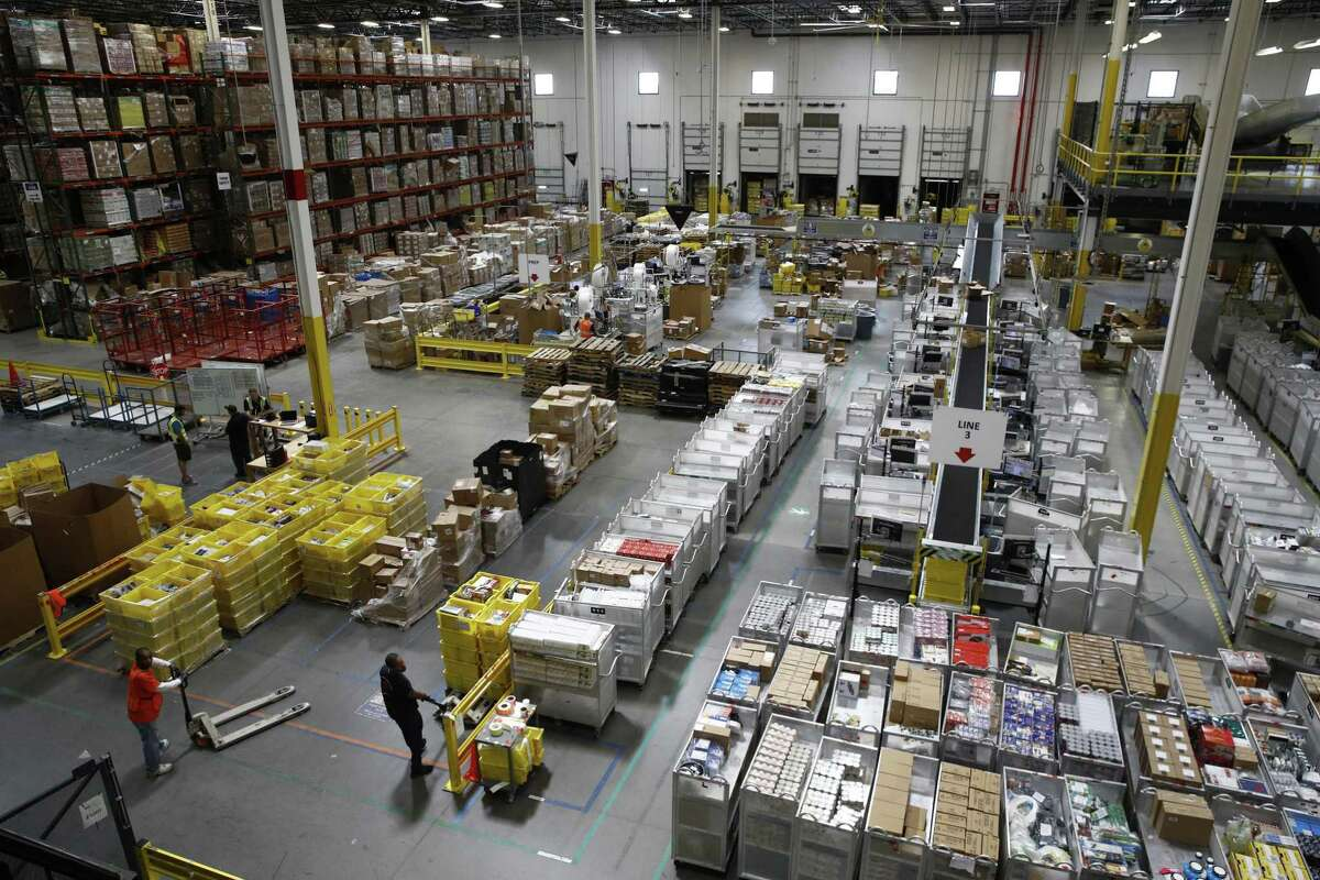 FILE- In this Aug. 3, 2017, file photo, workers prepare to move products at an Amazon fulfillment center in Baltimore. Amazon?'s announcement Tuesday, Oct. 2, 2018, that it will raise its minimum wage to $15 an hour will intensify the pressure on other companies to also lift their pay levels, particularly retailers and warehouse operators that are looking to staff up for the holidays. (AP Photo/Patrick Semansky, File)