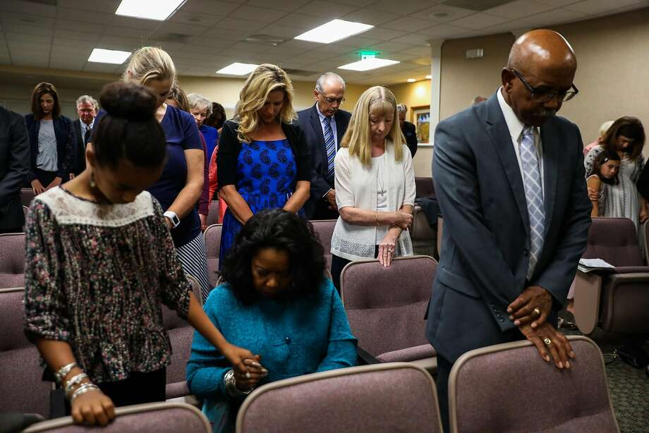 Astrid Granger (center, in white) prays with other members at the closing of church services at the Kingdom Hall of Jehovah's Witnesses in Santa Rosa. Photo: Gabrielle Lurie / The Chronicle