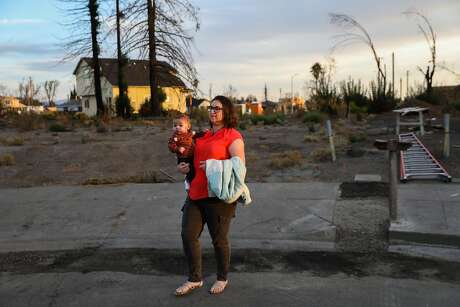 Melissa Geissinger and son Apollo Geissinger walk back to their car after taking a portrait at the site of their destroyed home after the Tubbs Fire tore through it last year in Santa Rosa, California, on Thursday, Sept. 27, 2018.