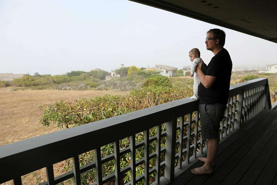 Cole Geissinger holds his son Ollie while giving a tour of their rental home in Bodega Bay on Saturday, August 18, 2018. Photo: Guy Wathen / The Chronicle