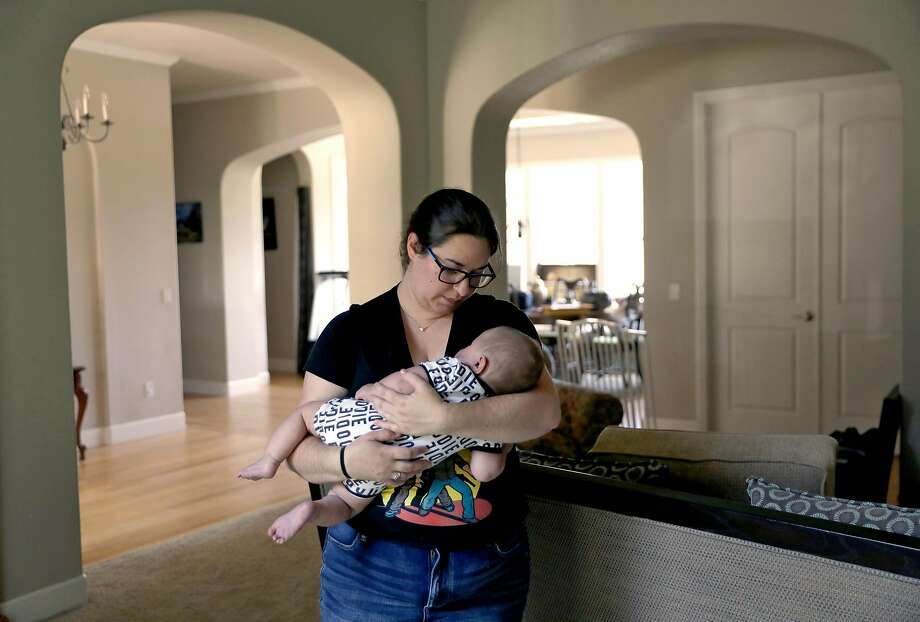 Melissa Geissinger holds her son Ollie in Sebastopol on Sunday, August 19, 2018. Geissinger and her husband Cole were in the process of completing their move to a rental home in Bodega Bay. Photo: Guy Wathen / The Chronicle