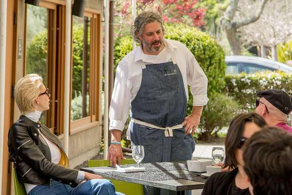 Chef Richard Reddington talks with people on the patio at  at Redd in Yountville, Calif., on March 22nd, 2015.