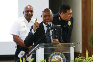 Houston mayor Sylvester Turner, center, stands at the podium as he holds a town hall with Houston Fire Department executive assistant chief Rodney West, left, and Houston Police chief Art Acevedo, right, in a collective attempt to convince the public to vote against a pay parity ballot measured for the Houston Fire Department Wednesday Sept. 19, 2018 in Houston.