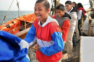 Rosely Martinez, 13, and her classmates from Curiale School in Bridgeport haul a line to raise a sail during a voyage on a replica of Amistad on Long Island Sound off Bridgeport on Tuesday.
