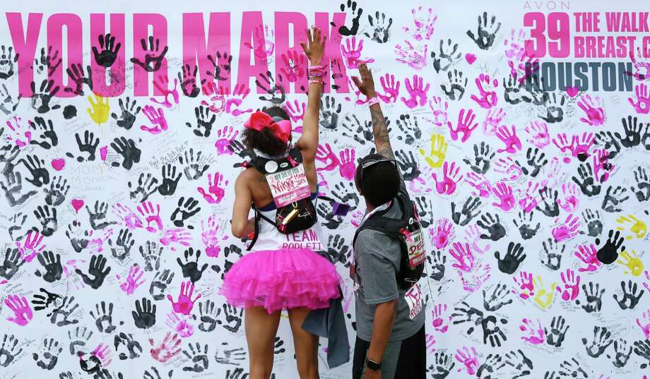 Unique Roden jumps up to leave a hand print with her partner Nikki Tripplett, a breast cancer patient, after completing the Avon 39 walk Sunday, April 24, 2016, in Houston. The pair had walked 39.3 miles in two days, before Tripplett's upcoming right mastectomy and hysterectomy. ( Jon Shapley / Houston Chronicle ) Photo: Jon Shapley, Staff / Houston Chronicle / © 2015  Houston Chronicle