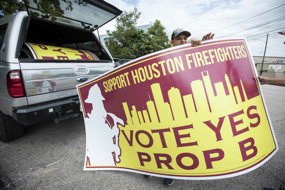 "Houston firefighter Josh Vogel takes a sign from his truck as he and other firefighters put up campaign signs supporting Proposition B, the pay ""parity"" item on the November ballot, on Tuesday, Sept. 25, 2018, in Houston."
