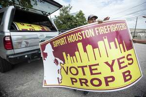 Houston firefighter Josh Vogel takes a Proposition B sign from his truck on Tuesday, Sept. 25, 2018, in Houston. Voters in November approved the measure requiring the city to pay firefighters the same as police of corresponding rank and seniority.