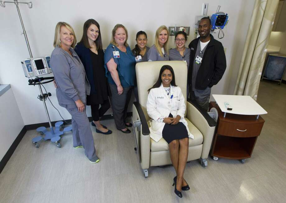From left to right Cheryl Leheny, Lindsey Pimentel, Whitney Arriaga, Buena Delacruz, Kim Gensler, Ariana Arrambide, Kardaryl Wallace and Dr. Priya Ramshesh (sitting) pose for a photo at Houston Methodist The Woodlands Hospital on Thursday, Sept. 13, 2018, in The Woodlands. This group is the staff of the Infusion Center at HMTW. Because they become so close when their patients, they get creative with celebrations for their patients who have completed their cancer treatment. Photo: Jason Fochtman, Houston Chronicle / Staff Photographer / © 2018 Houston Chronicle