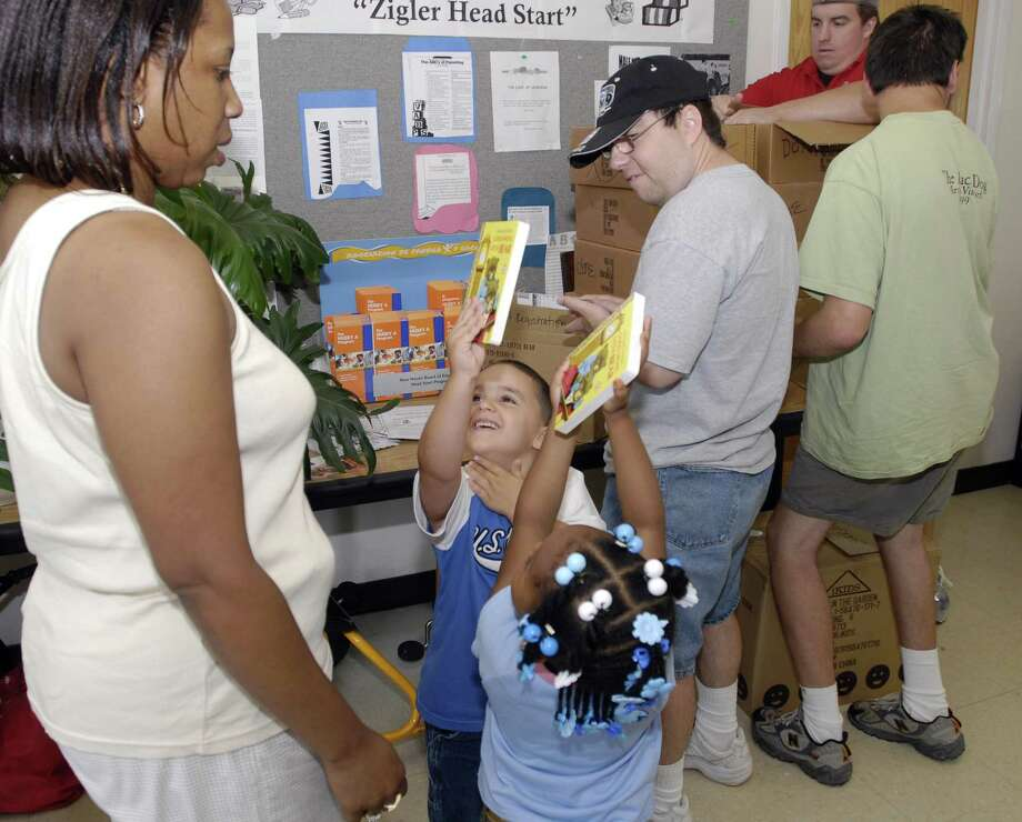 Dennis Mederios, 5, second from left, and Tyeanna Hunter, 4, both of New Haven, show off new  books to their Head Start teacher Michelle Streater after a delivery of 500 new books donated by the Connecticut Read to Grow book bank in Branford to the Zigler Head Start Center in New Haven. Photo: Hearst Connecticut Media File
