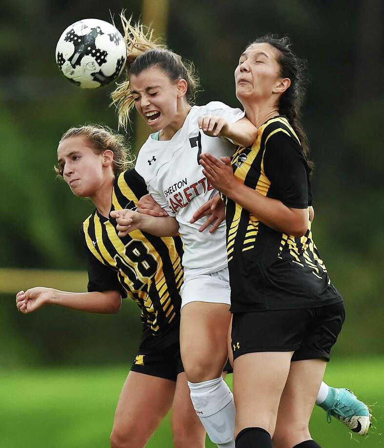 Shelton's Devan Wildman wins a header during a battle against Amity's Nicole Grosso (18) and Kayla Morgan on Tuesday. Photo: Catherine Avalone / Hearst Connecticut Media / New Haven Register
