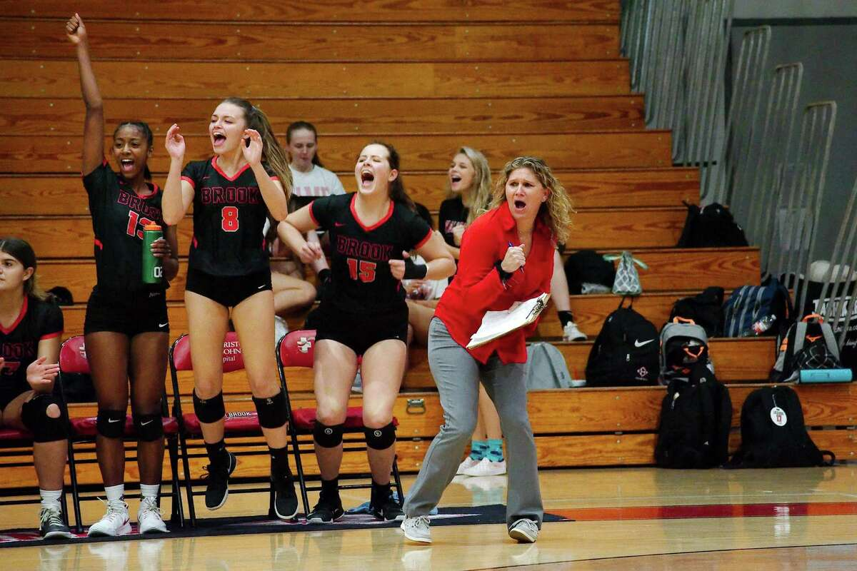 Clear Brook's Kennedy Crutchfield (13), Kayleigh Shultz (8), Mayce Barker (15) and Lady Wolverine head volleyball coach Meredith Thompson celebrate a point against Clear Creek.