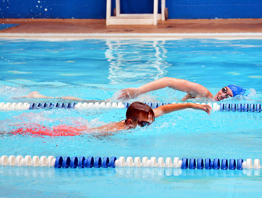 PRACTICE MAKES PERFECT   Plainview swim coach Andrea Bond (right) completes laps in the pool with one of her swimmers during practice on Friday at the Plainview YMCA. Plainview's team will open the short-course season at Lubbock this weekend. Photo: Alexis Cubit/Plainview Herald