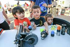 Aaron Pollorena, Oscar Pollorena and Olivia Pollorena learn about equipment used by the CBP Special Response Team at the Sames Auto Arena on Oct. 2, 2018 during National Nigh Out.