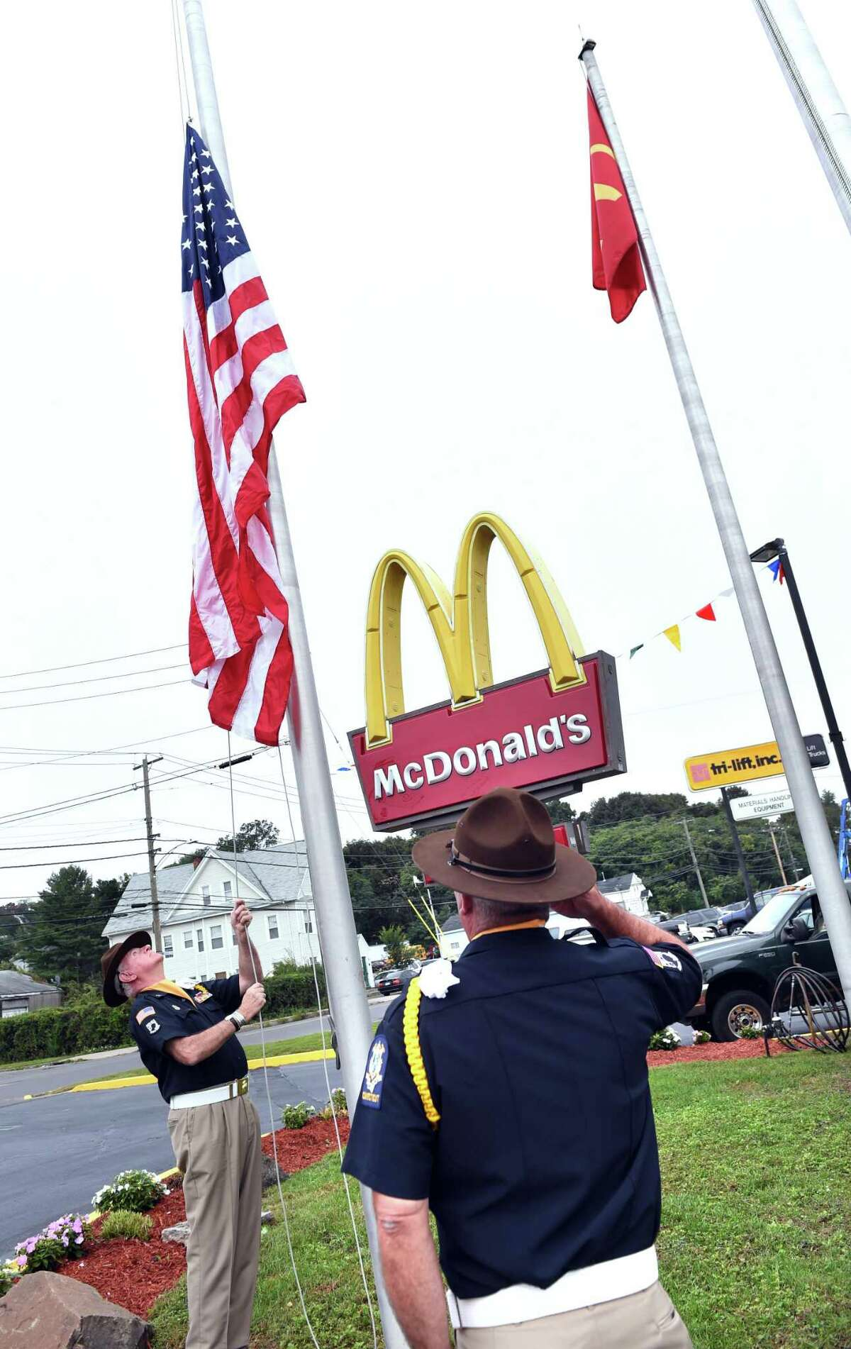 Jim Botsacos (right) salutes as Steve Fahy of the State of Connecticut American Legion Color Guard raises the United States flag at the grand re-opening of the East Haven McDonald's on October 2, 2018.
