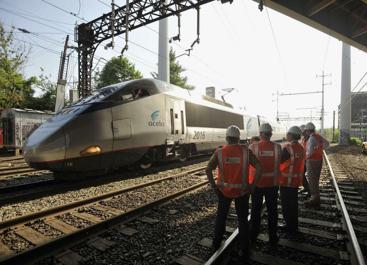An Acela train operator waves to officials surveying the scene in Bridgeport.
