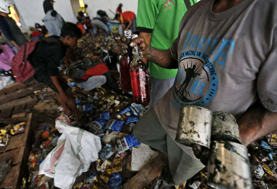 A man holds bottles of syrup and cans of milk scavenged from an abandoned warehouse in Palu. Photo: Dita Alangkara / Associated Press