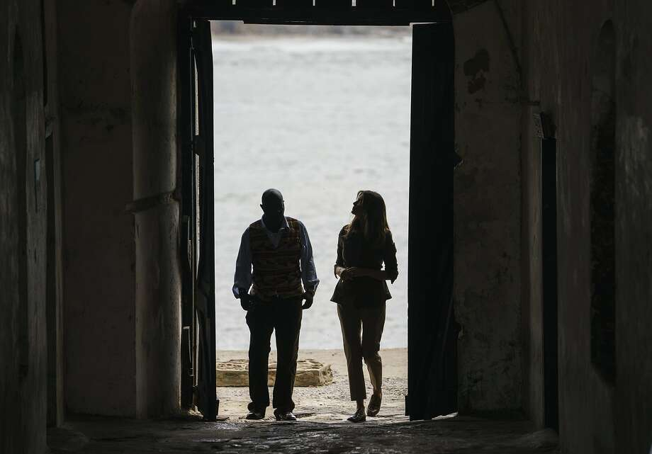 "First lady Melania Trump looks up as she walks through the ""Door Of No Return"" with a museum educator at a holding facility for slaves shipped to the New World on Ghana's coast. Photo: Carolyn Kaster / Associated Press"