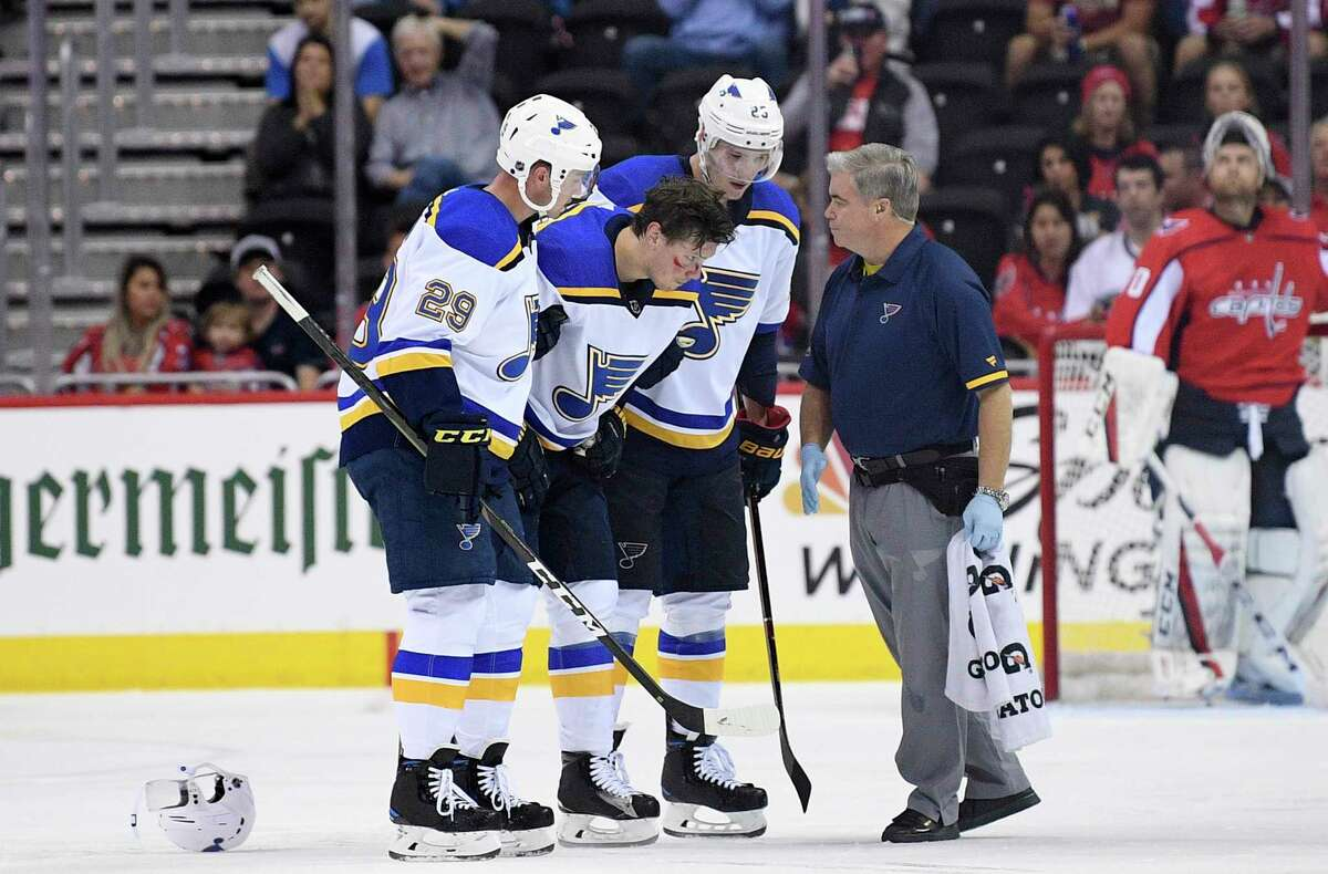 St. Louis Blues center Oskar Sundqvist, second from left, is helped off the ice by right wing Dmitrij Jaskin (23) and defenseman Vince Dunn (29) during the second period of an NHL preseason hockey game after he was checked by Washington Capitals' Tom Wilson, Sunday, Sept. 30, 2018, in Washington. (AP Photo/Nick Wass)