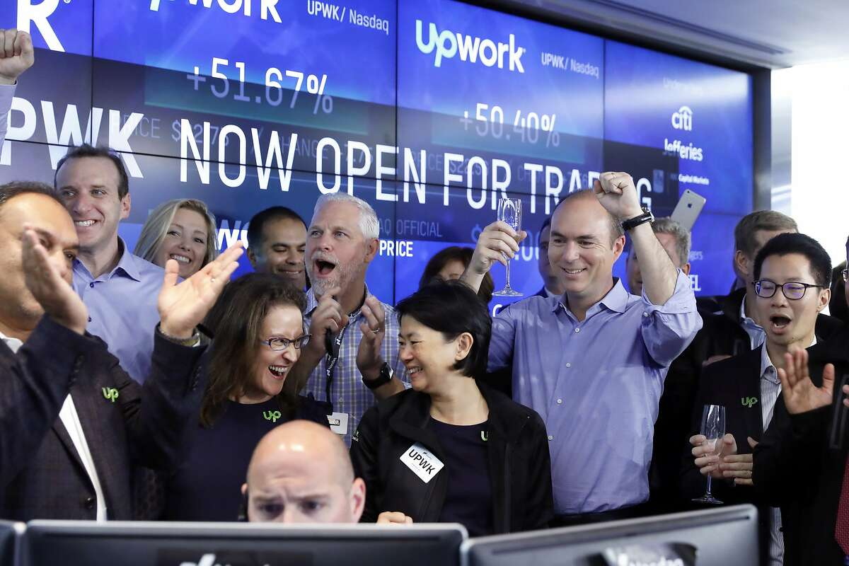 Upwork Inc. President & CEO Stephane Kasriel second from right, joins the celebration as his company's IPO begins trading at the Nasdaq MarketSite, in New York's Times Square, Wednesday, Oct. 3, 2018. (AP Photo/Richard Drew)