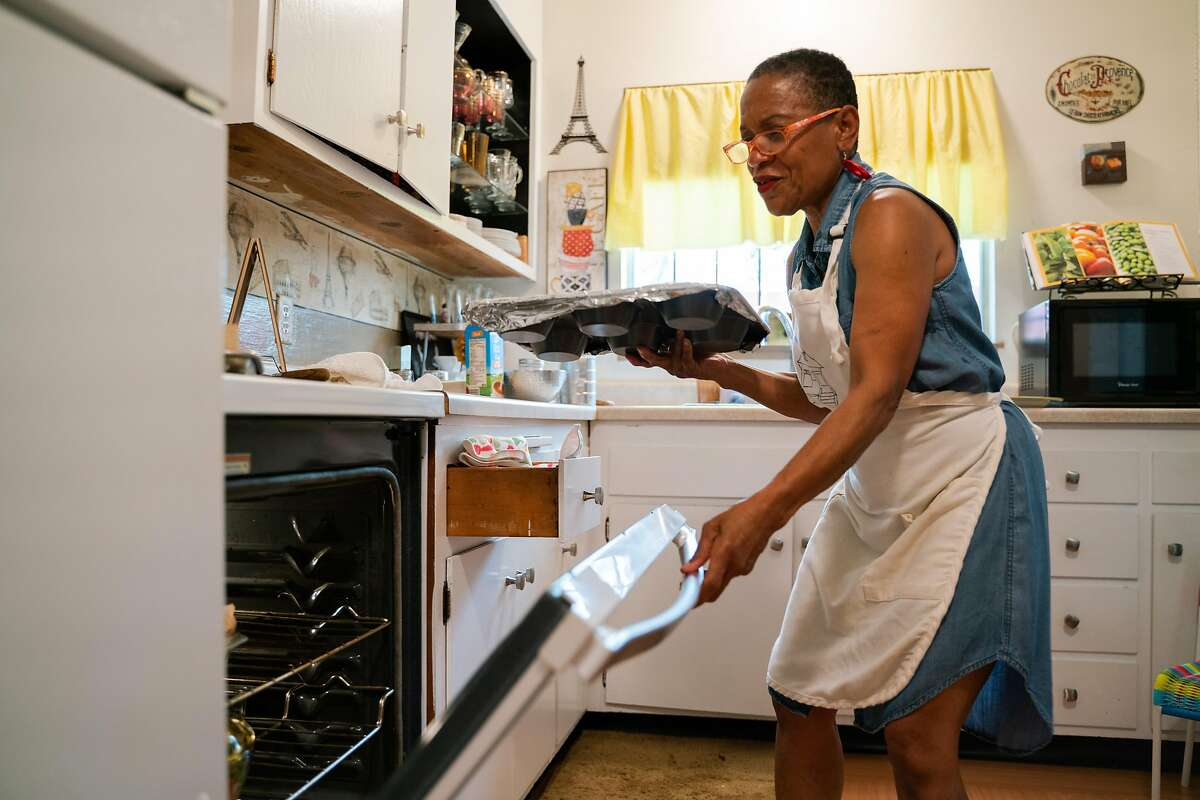 """Renee McGhee, 62, puts bread pudding into the oven at her home in Berkeley, Calif., on Tuesday, October 2, 2018. The community around McGhee helped her heal after she experienced two arm surgeries. """"I began developing relationships with people,"""" said McGhee. """"It got to a place where they became family."""""""