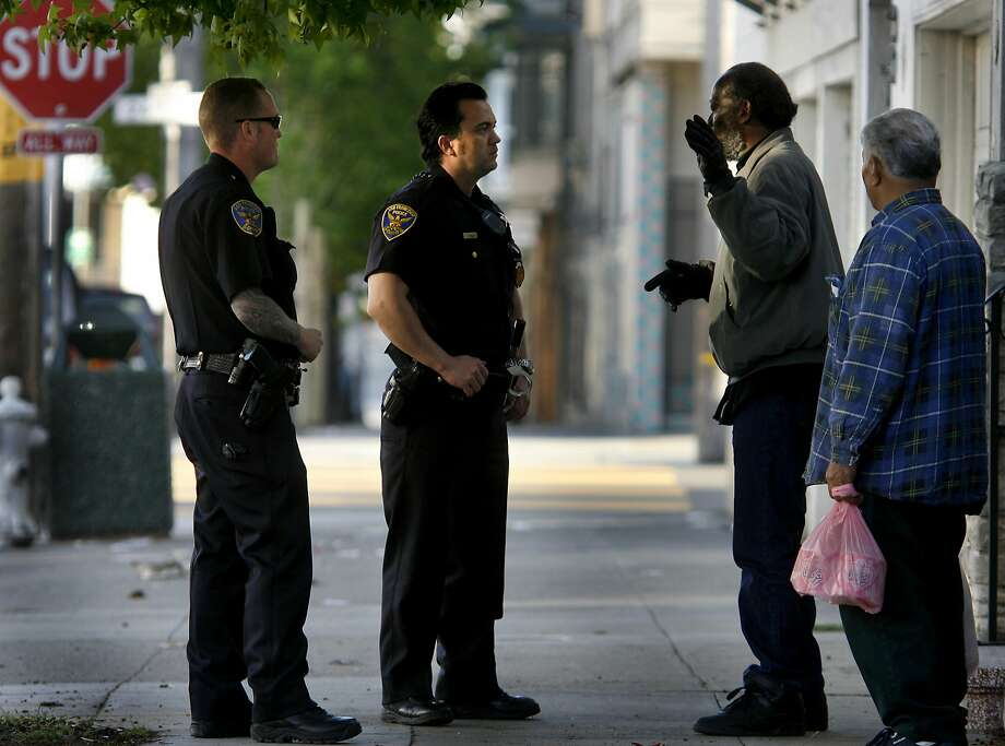 S.F. Police Officers Rain Daughtery (far left) and Pete Shields  speak with two men in the Mission. Photo: Brant Ward / The Chronicle 2007