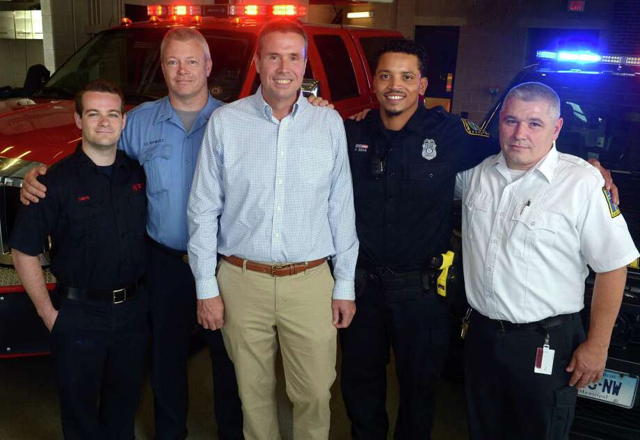 Norwalk resident Todd Boe, center, and his rescuers, Norwalk Firefighter Sean Davis, Norwalk Fire Department Lieutenant Scott Rywolt, Norwalk Police Officer Jose Silva and Norwalk Hospital Paramedic Eric Hebert, at Norwalk Fire Department Headquarters Wednesday, October 3, 2018, in Norwalk, Conn. Boe had a heart attack while out running this summer and the first responders performed CPR for more than 20 minutes. First police, then Norwalk firemen and ultimately EMS from Norwalk Hospital. Boe survived a very serious heart event and is now doing well after heart surgery. Photo: Erik Trautmann / Hearst Connecticut Media / Norwalk Hour