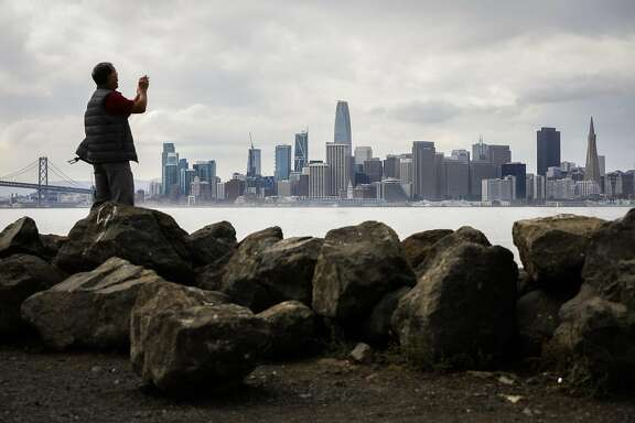 Liem Phan of Oakland takes a photo of the skyline from Treasure Island in San Francisco, California, on Wednesday, Oct. 3, 2018.