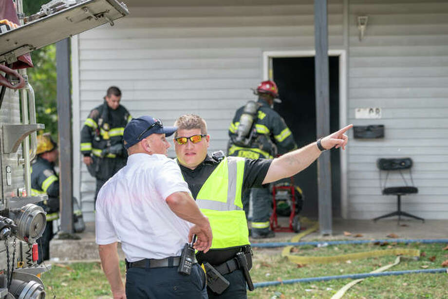 Alton Fire Chief Bernie Sebold speaks with an Alton police officer Wednesday afternoon while crews work to extinguish a fire in the bedroom of a two-story home at 1508 Central Ave. Photo: Nathan Woodside | The Telegraph