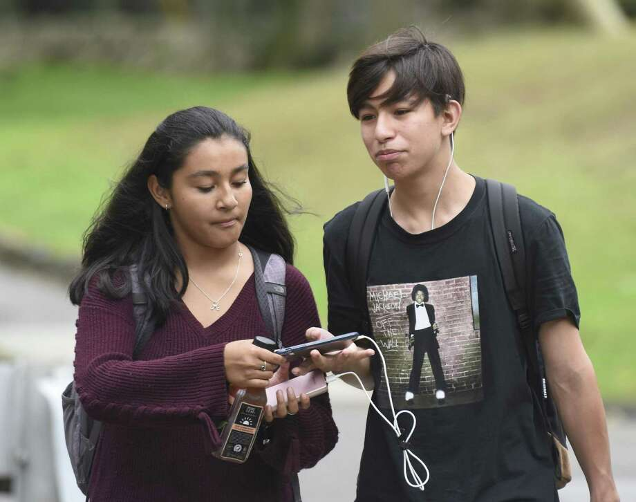 GHS sophomores Krista Beltran and Axel Rivas use a cell phone while walking back to Greenwich High School in Greenwich, Conn. Wednesday, Oct. 3, 2018. Schools in Greenwich do not have an altogether ban on cell phones in school, but instead judge cell phone use on a case by case basis. Photo: Tyler Sizemore / Hearst Connecticut Media / Greenwich Time