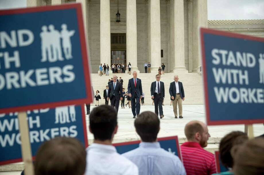 From left, Liberty Justice Center's Director of Litigation Jacob Huebert, Illinois Gov. Bruce Rauner, Liberty Justice Center founder and chairman John Tillman, and plaintiff Mark Janus walk out of the the Supreme Court after the court rules in a setback for organized labor that states can't force government workers to pay union fees in Washington, Wednesday, June 27, 2018. (AP Photo/Andrew Harnik) Photo: Andrew Harnik / Copyright 2018 The Associated Press. All rights reserved