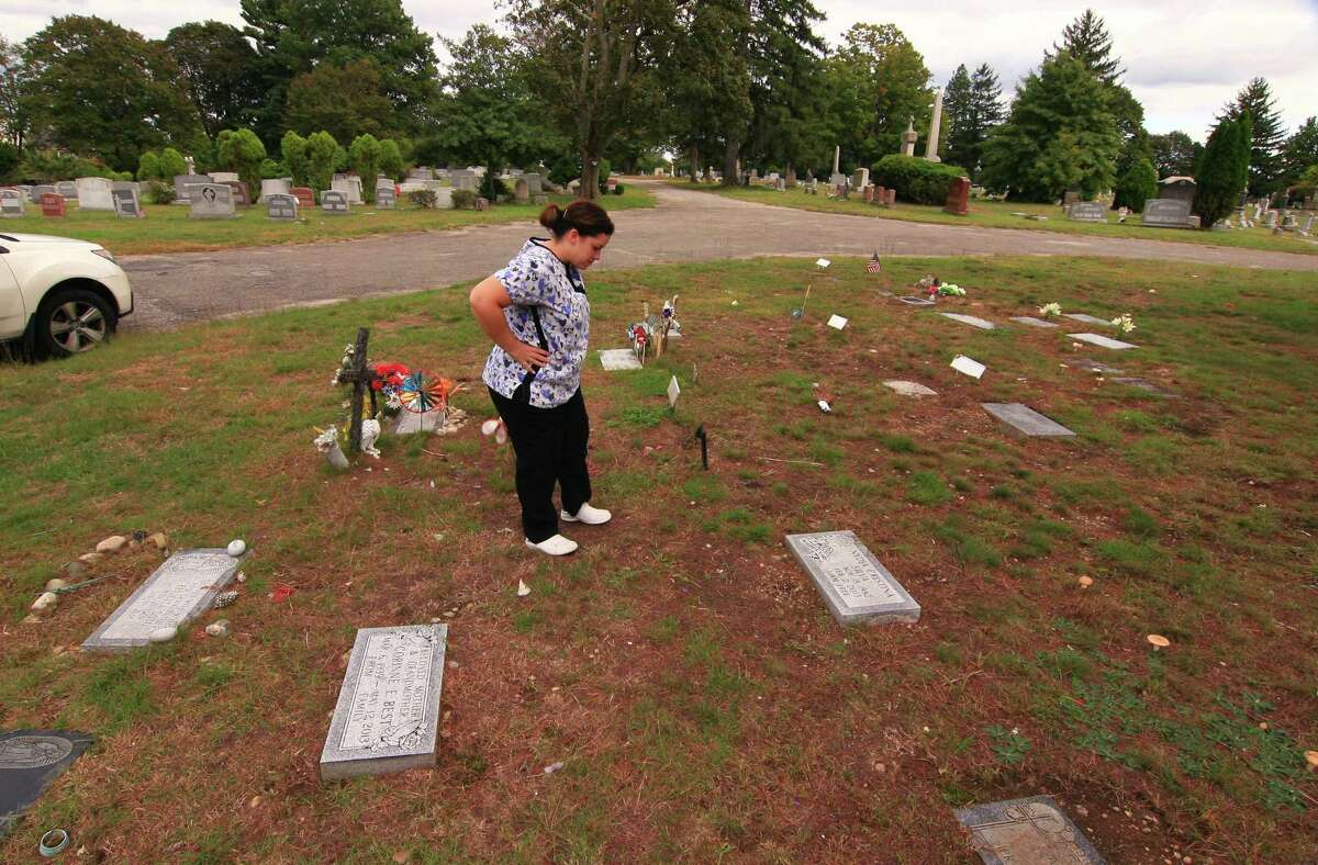 Damaris Ortiz, of Ansonia, checks on her sister's grave at Park Cemetery in Bridgeport, Conn., on Wednesday, Oct. 3, 2018. This particular spot called Founder's Circle is not supposed to have any people buried there. It is also believed that some older graves and grave markers in the cemetery have been moved in effort to make way for newer burials.