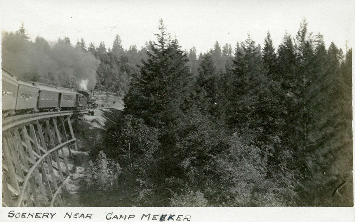"""Caption: """"Scenery Near Camp Meeker,"""" c. 1906. Train crossing trestle at left side of photograph, with trees and other vegetation occupying most of the photograph's area. Camp Meeker, in Sonoma County north of San Francisco, is in the California Coast Ranges. Established by lumber baron Melvin Cyrus Meeker in 1866, by the turn of the twentieth century the area primarily served as a vacation and resort destination. """"McCarthy Album 05, Photograph 025,"""" California State Archives Exhibits, accessed October 3, 2018"""
