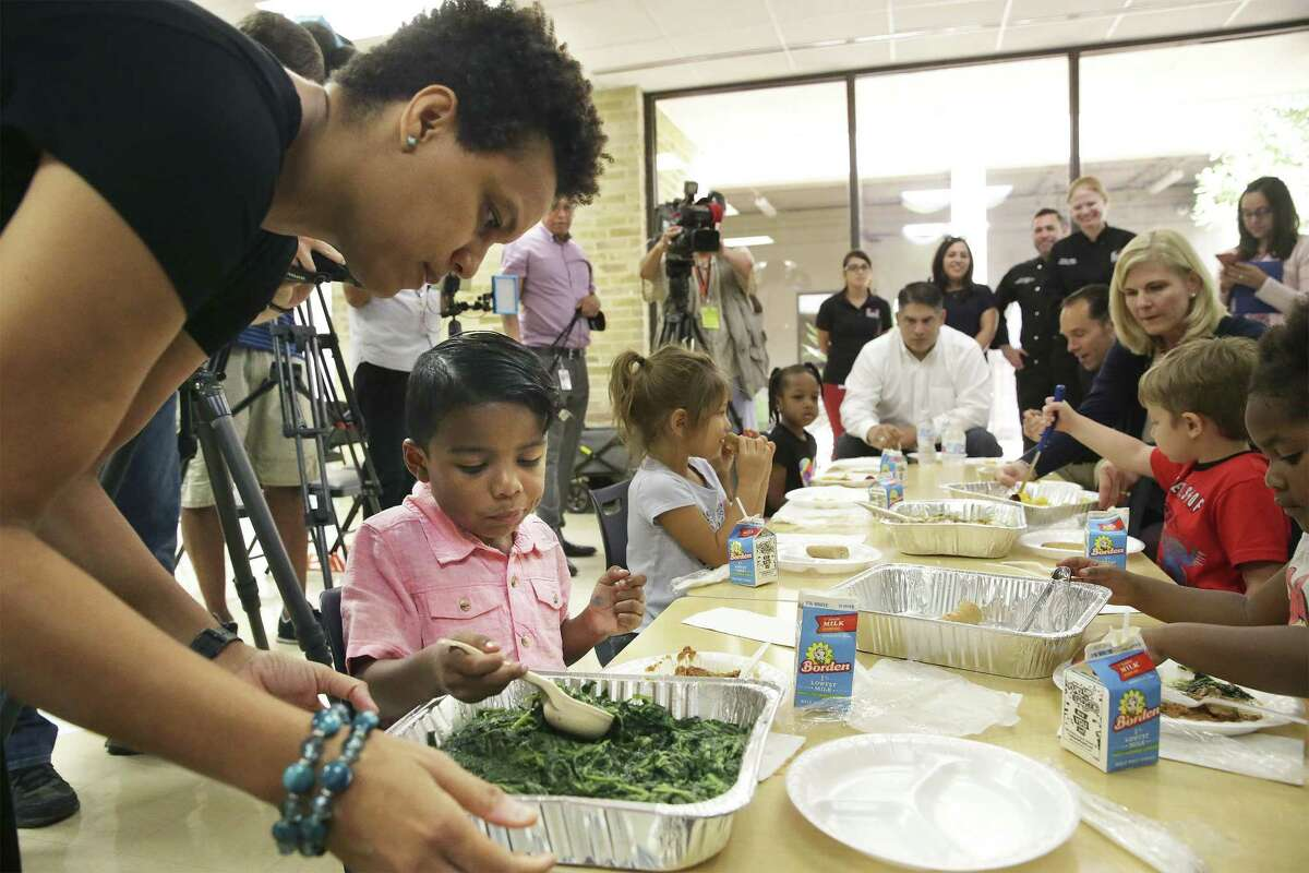 Instructional specialist Chaka Burroughs helps Andre serve himself greens Wednesday as Pre K 4 SA announces it has partnered with the Food Bank to provide the students' meals.
