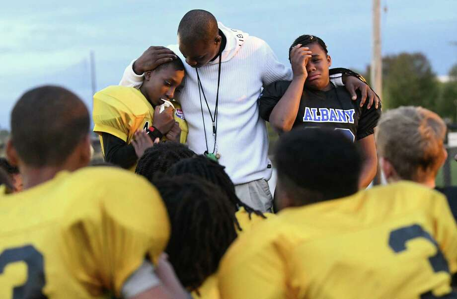 Coach Damin Waring comforts players Tyreek Johnson, left, and Diamond Williams as players came up one by one to talk about coach Joseph Davis during Pop Warner football practice at Foley Field on Wednesday, Oct. 3, 2018 in Albany, N.Y. This is the first team practice since the head coach Joseph Davis was killed in a shooting over the weekend. (Lori Van Buren/Times Union) Photo: Lori Van Buren, Albany Times Union / 20045021A