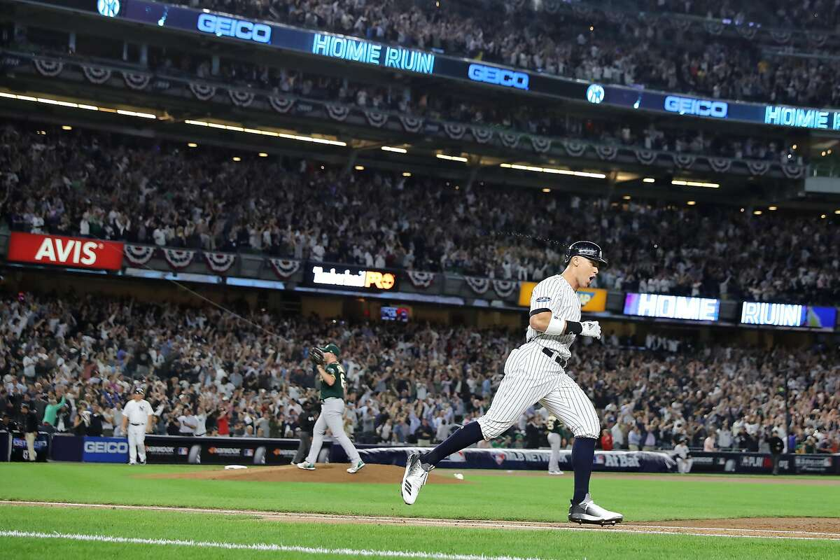 NEW YORK, NEW YORK - OCTOBER 03: Aaron Judge #99 of the New York Yankees celebrates after hitting a two run home run against Liam Hendriks #16 of the Oakland Athletics during the first inning in the American League Wild Card Game at Yankee Stadium on October 03, 2018 in the Bronx borough of New York City. (Photo by Elsa/Getty Images)