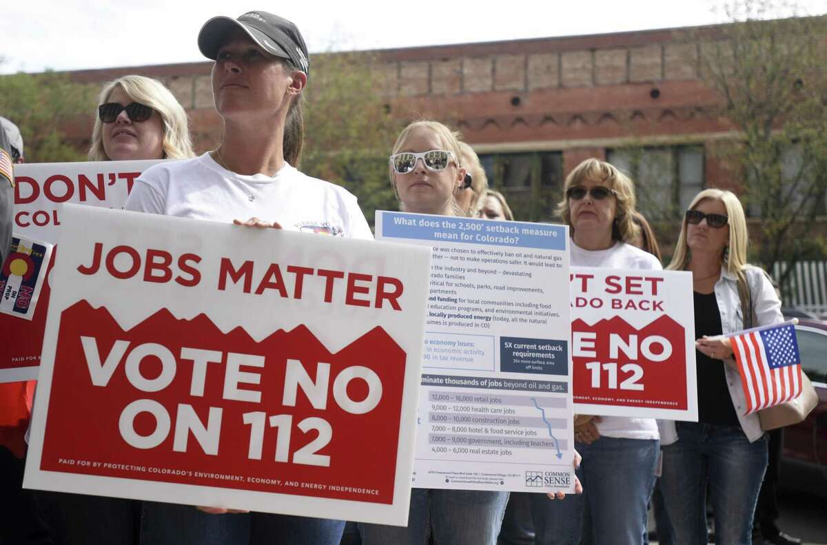 A crowd begins to form behind Stephanie Dionne as she and others hold signs urging others to vote against Proposition 112 during a rally put on by the Mayors Against Proposition 112 on Thursday, Sept. 20, 2018 at the Weld County Courthouse in Greeley. The event hosted mayors from several northern Colorado cities voicing their concerns about Proposition 112.