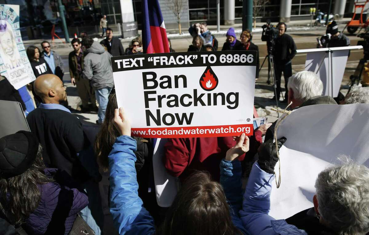 Fracking has been controversial issue in Colorado for years. In this 2015 photo, an activist waves a placard calling for the ban of fracking during a news conference in Denver.