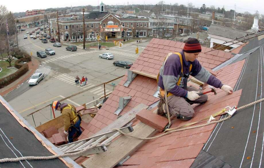 Marrillio Costa, at right, and Ron Vitti, below, both of Barrett Roofing in Danbury, work together to install slate tiles onto the roof of the Fairfield Public Library in Fairfield on Dec. 29th, 2004. Photo: Christian Abraham / Connecticut Post