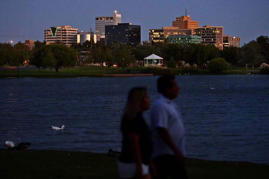 The Midland skyline is visible as a couple walks around the pond after sunset at Wadley-Barron Park, Oct. 3, 2018. James Durbin/Reporter-Telegram Photo: James Durbin