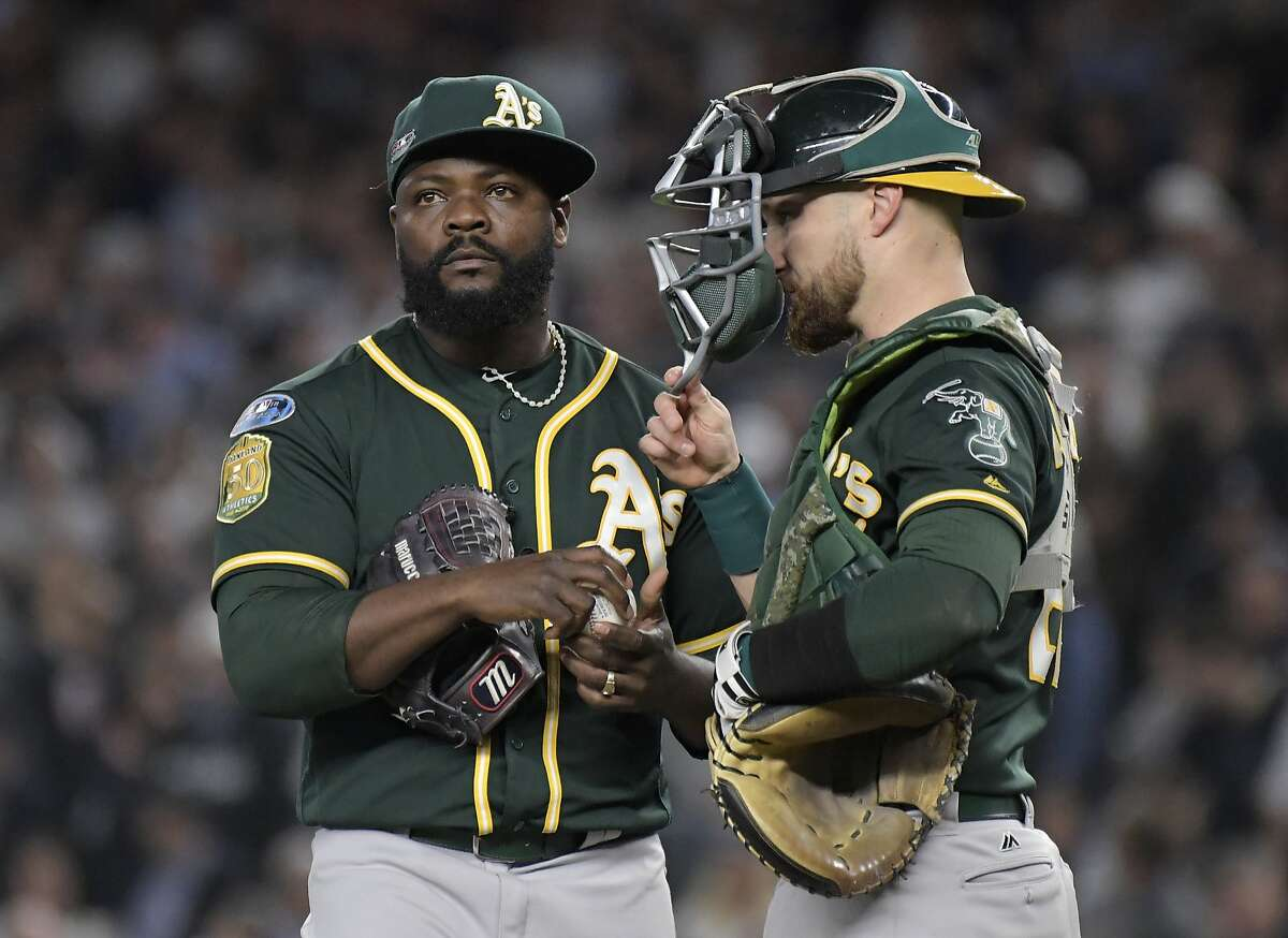Oakland Athletics relief pitcher Fernando Rodney, left, and catcher Jonathan Lucroy wait on the mound as Rodney is relieved during the sixth inning of the American League wild-card playoff baseball game against the New York Yankees, Wednesday, Oct. 3, 2018, in New York. (AP Photo/Bill Kostroun)