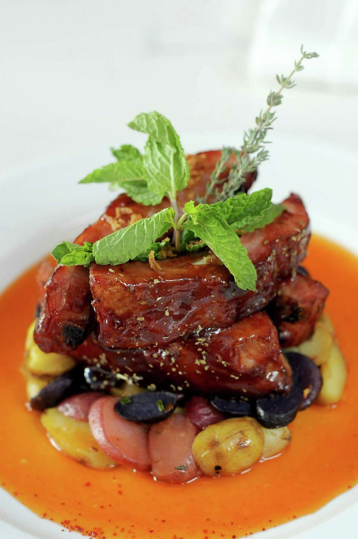 Roasted pork ribs with candied goose fat, sweet peppers sauce and roasted potatoes at La Villa Saint-Tropez restaurant in Montrose.