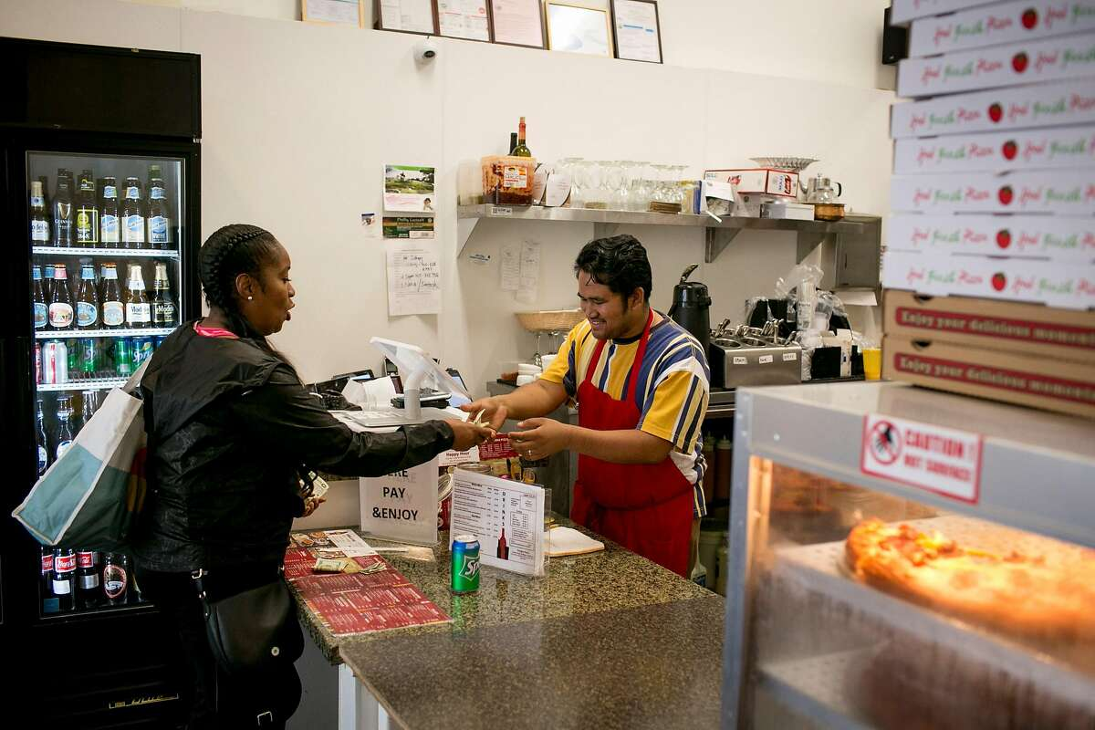 Santosh Gurung serves a customer at Himalayan Pizza and Momo, a Nepalese restaurant in the Tenderloin, Wednesday, Sept. 12, 2018 in San Francisco, Calif.