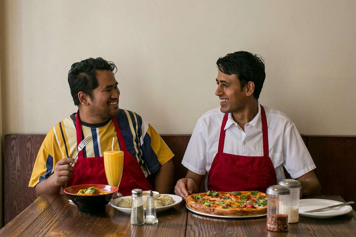 From left, Santosh Gurung and Naba Dhakal, owners of Himalayan Pizza and Momo, sit at a table in their Nepalese restaurant in the Tenderloin Wednesday, Sept. 12, 2018 in San Francisco, Calif.