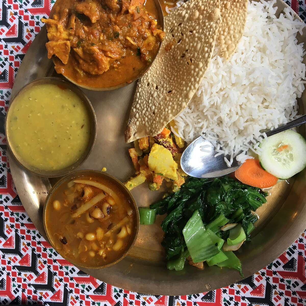 Red Chilli, a resataurant in San Francisco's Tenderloin neighborhood, serves a Nepalese thali with chicken curry, lentils, sauteed mustard greens, potatoes with bamboo shoots and black-eyed peas, and pickle.