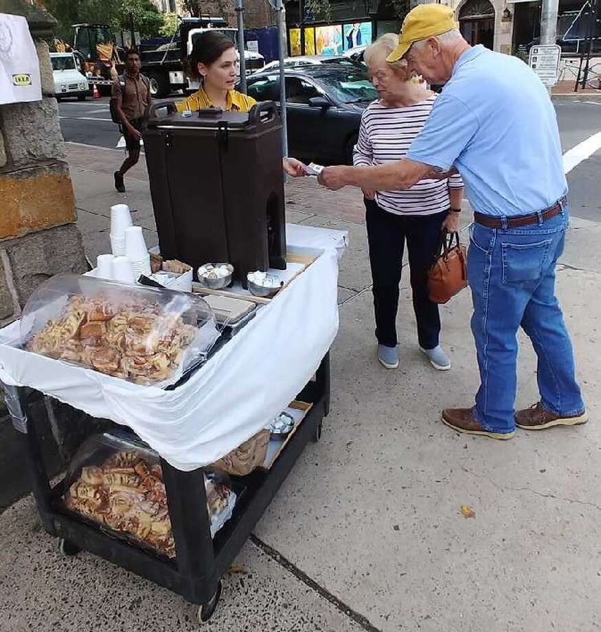 IKEA managers hand out cinnamon buns Thursday on the corner of Elm and York streets. Photo: Courtesy Of IKEA