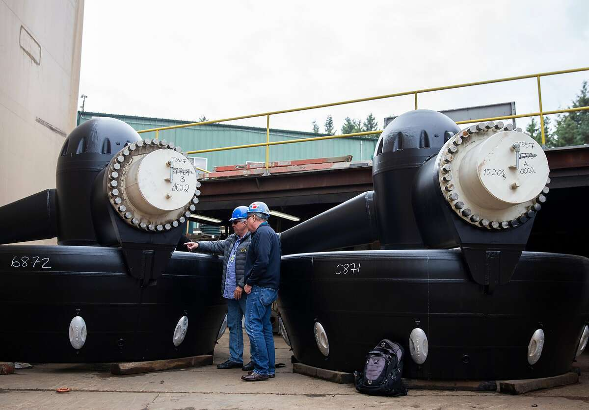Peter Zwart, VP of Operations for Baydelta Maritime and Matt Nichols, EVP of Nichols Brothers Boat Builders, take a look at the boat's two US255 azimuth thrusters at Nichols Brothers Boat Builders on Whidbey Island, Monday, Sept. 17, 2018 in Freeland, Washington. The multipurpose tractor tugboat will be the first with a hybrid propulsion system used on the West Coast, using a Rolls-Royce Z-drive that can operate as full diesel, full electric or as diesel-electric.