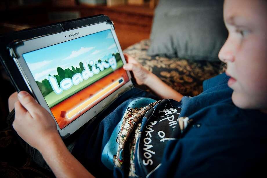 Shane Slingerland of Lethbridge, Alberta, uses apps on his tablet. Some legislators say apps for children are too invasive. Photo: Bryce Meyer / New York Times