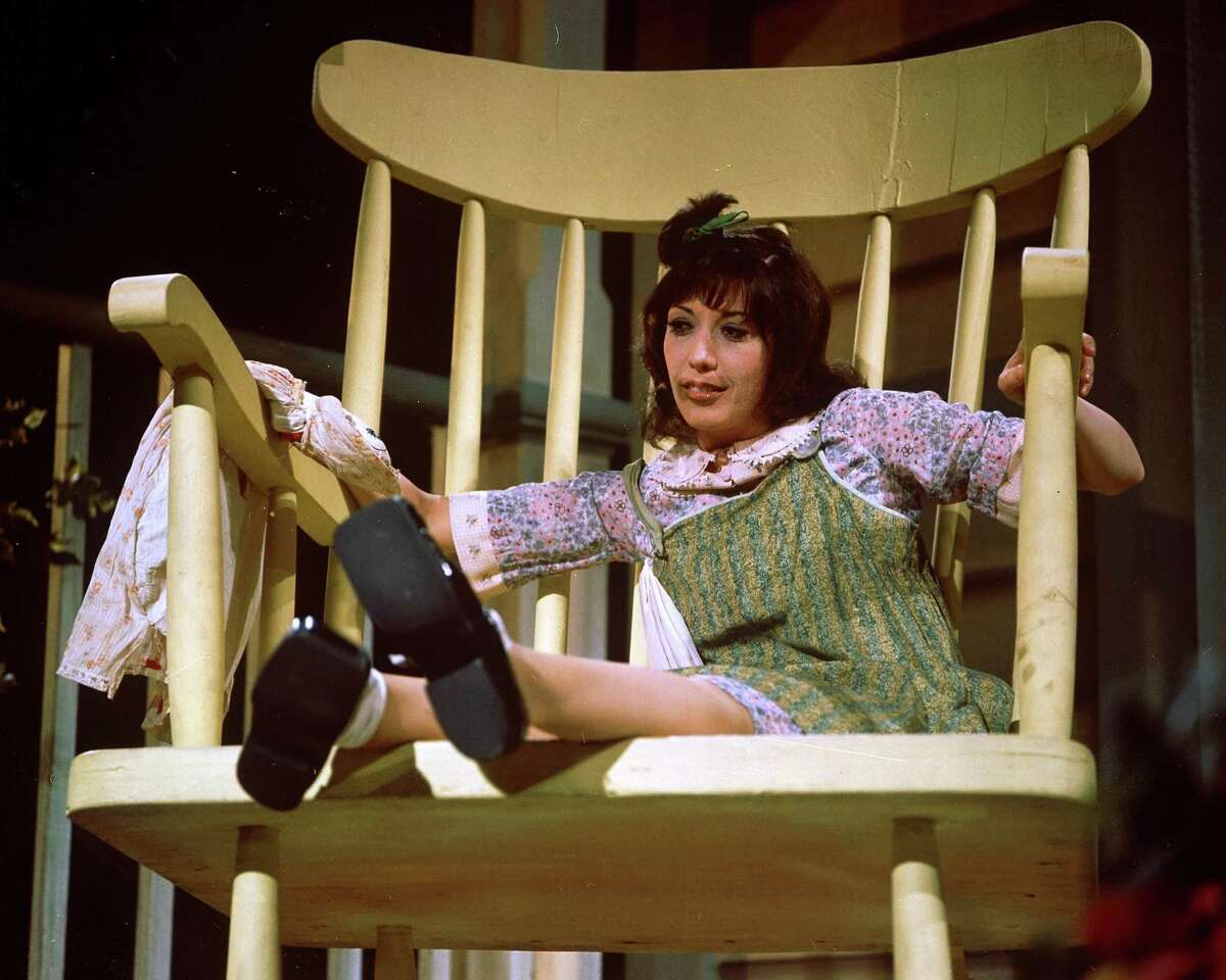 American actress and commedienne Lily Tomlin sits in an oversize chair as the character Edith Ann in her first television special 'Lily,' filmed October 22, 1973. The show, which aired November 2, 1973, featured Tomlin in a variety of roles including the little girl Edith Ann. (Photo by CBS Photo Archive/Getty Images)