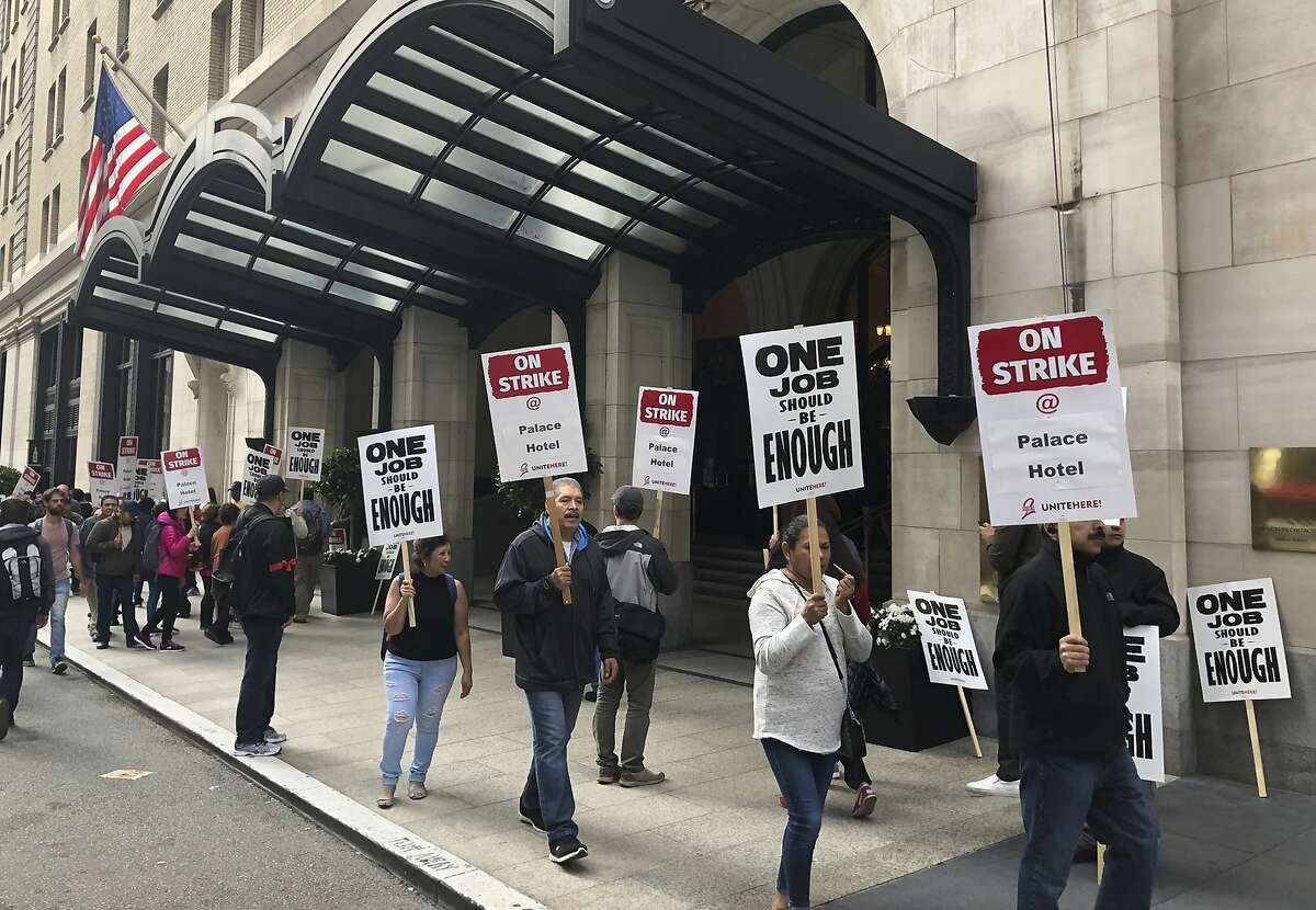 Hotel workers strike outside the Palace Hotel in San Francisco, Calif., Thursday, Oct. 4, 2018. Thousands of housekeepers, cooks and other Marriott hotel workers are on strike in San Francisco and San Jose after months of negotiating for a wage increase. (AP Photo/Juliet Williams)